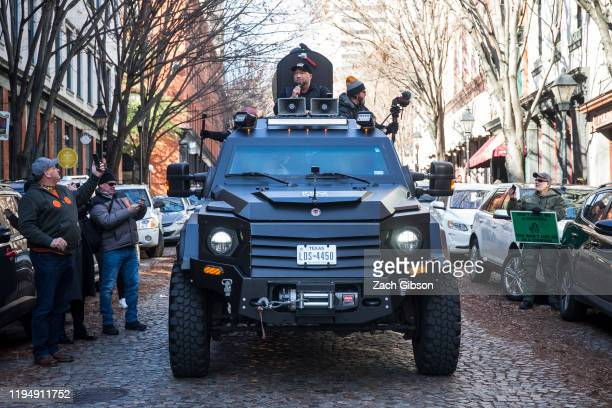 InfoWars host Alex Jones rides in an armored vehicle during a rally organized by The Virginia Citizens Defense League on Capitol Square near the...