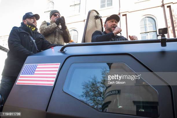 InfoWars host Alex Jones rides in an armored vehicle with Patriot Prayer founder Joey Gibson during a rally organized by The Virginia Citizens...