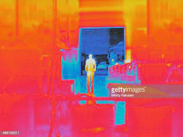Infra red heat image of worker and heat loss from loading doors in factory