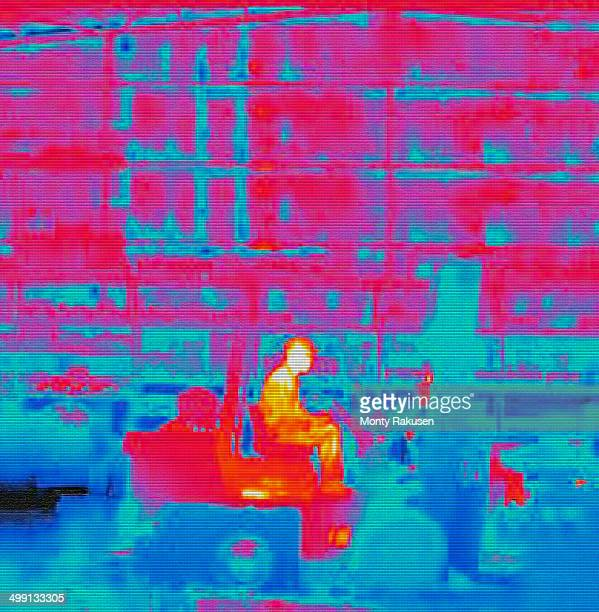 Infra red heat image of worker in fork lift truck in factory