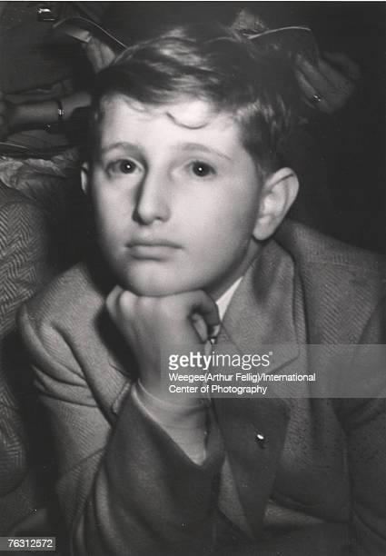 Infrared close-up of a young boy in a blazer who rests his chin on his hand as he watches a circus, New York, New York, 1940s.