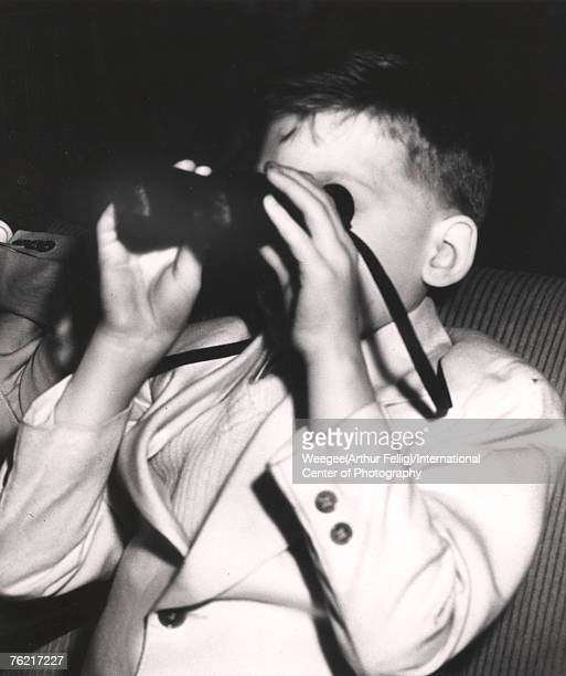 Infrared photograph of a young boy in a lightcolored blazer who watches a movie through a pair of binoculars New York New York early 1940s Photo by...