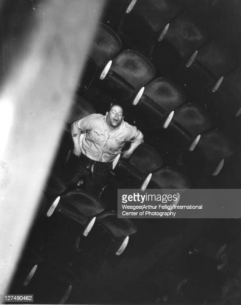 Infrared view, looking down from the balcony, of a man asleep in a movie theatre, New York, New York, mid 20th century.
