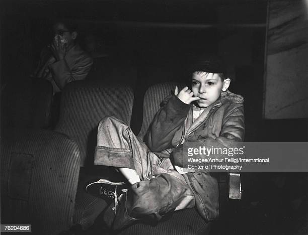Infrared view of a boy as he chews his finger and he watches a movies in a theatre New York New York ealry 1940s Photo by Weegee/International Center...