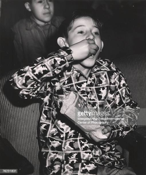 Infrared view of a boy as he eats popcorn and watches a movie, New York, NEw York, early 1940s.
