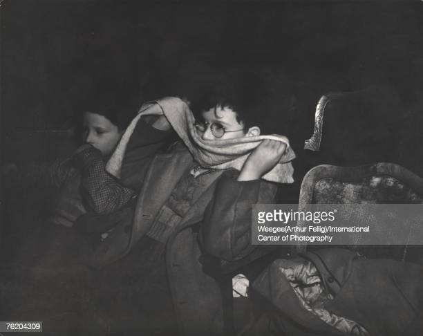 Infrared view of a boy with eyeglasses who holds a scarf over his mouth as he watches a movie in a theatre New York New York early 1940s Photo by...