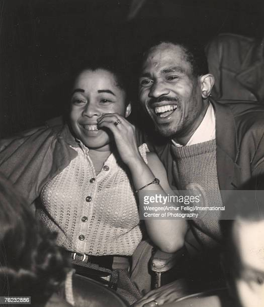 Infrared view of a couple who laugh together at a movie in a theater, New York, New York, early 1940s.