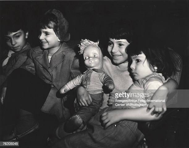 Infrared view of a girl who smiles as she watches a movie with one arm around her sistser the other around a doll next to them two other children...