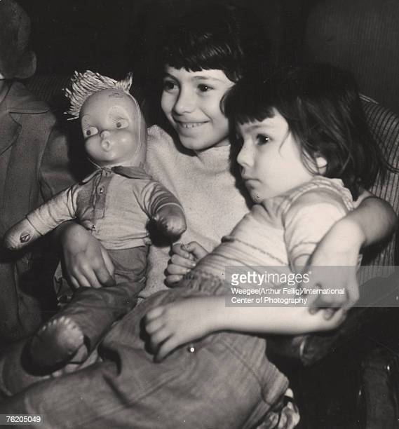 Infrared view of a girl who smiles as she watches a movie with one arm around her sistser the other around a doll early 1940s Photo by...