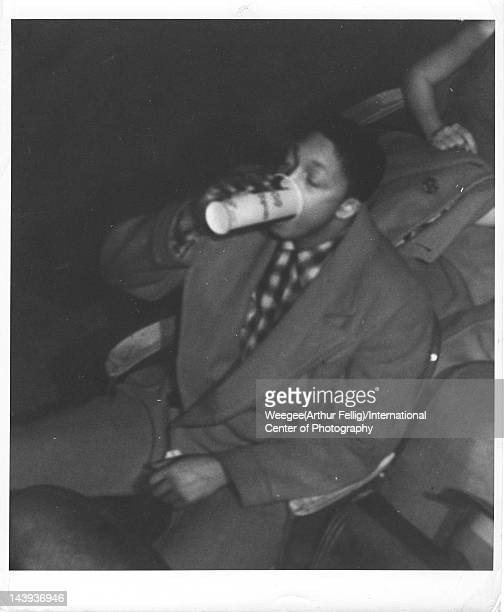Infrared view of a man as he drinks from a concession stand paper cup in a movie theater twentieth century Photo by Weegee /International Center of...