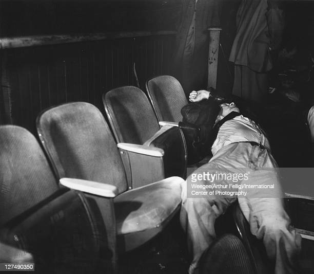 Infrared view of a man asleep stretched across two rows of seats in a movie theatre New York New York mid 20th century Photo by Weegee/International...
