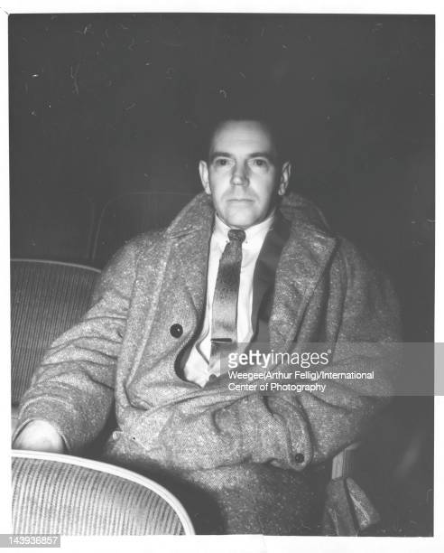 Infrared view of a man one hand in his coat pocket as he sits in a movie theater twentieth century Photo by Weegee /International Center of...