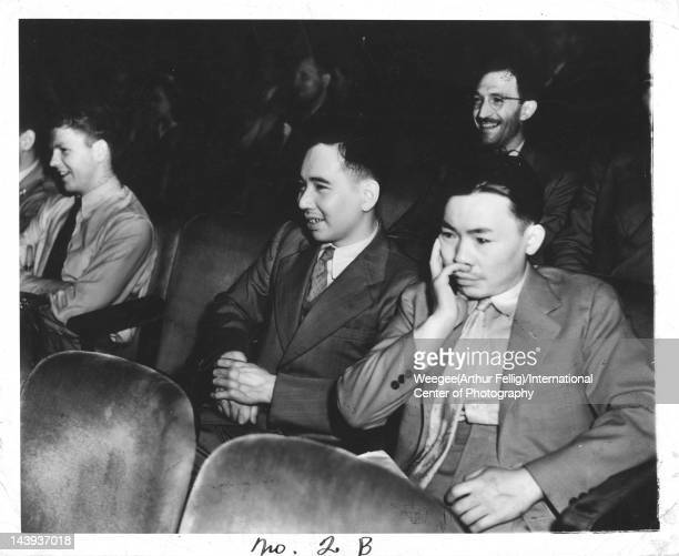Infrared view of a several men as they laugh in a movie theater, twentieth century.