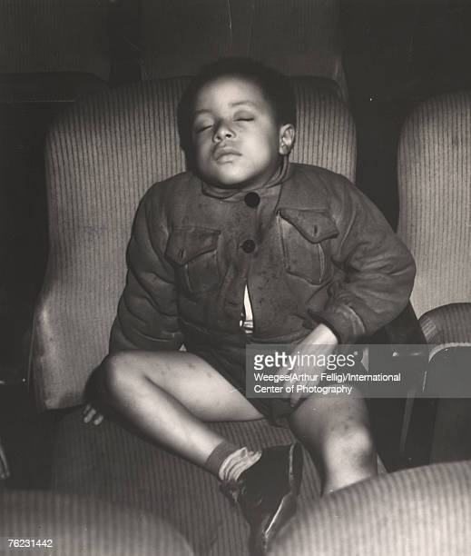 Infrared view of a young boy asleep in a movie theatre seat, New York, New York, early 1940s.