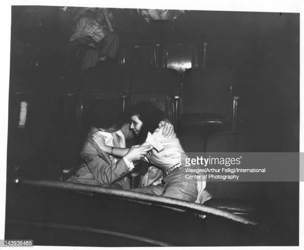 Infrared view of a young couple as they embrace seated side by side in the audience at the Palace Theater ca 1943 Photo by Weegee /International...