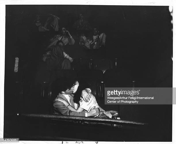 Infrared view of a young couple as they kiss seated side by side in the audience at the Palace Theater ca 1943 Photo by Weegee /International Center...