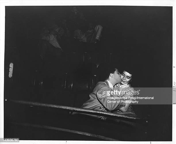 Infrared view of a young man as he kisses his date, seated side by side in the audience at the Palace Theater, ca. 1943.