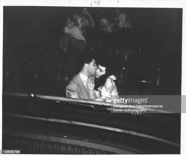 Infrared view of a young man as he kisses his date seated side by side in the audience at the Palace Theater ca 1943 Photo by Weegee /International...