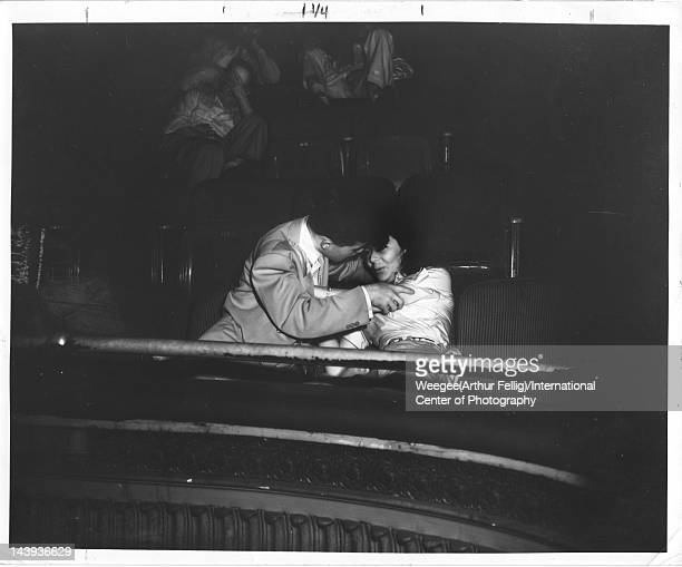 Infrared view of a young man as he leans in to kiss his date seated side by side in the audience at the Palace Theater ca 1943 Photo by Weegee...