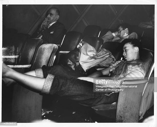 Infrared view of a young woman asleep in a movie theatre, twentieth century.