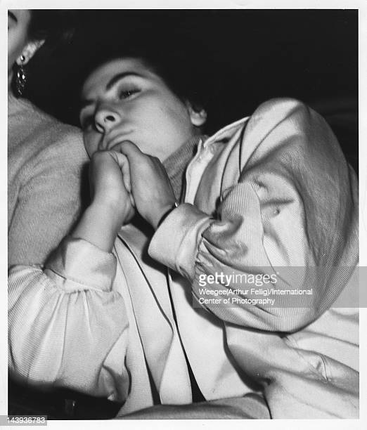 Infrared view of a young woman, hands clasped, as she leans on her companion in a movie theatre, twentieth century.