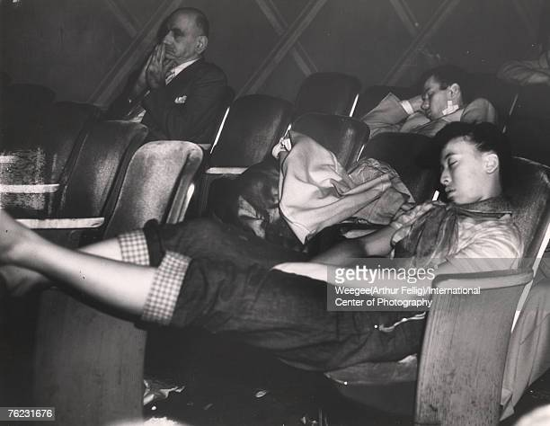 Infrared view of a young woman who sleeps in a movie theatre with her legs propped up on the arm of the seat in front of her early 1940s A man in a...