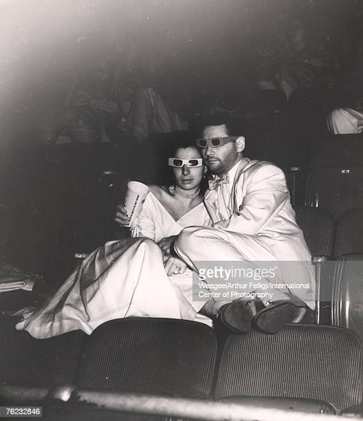 Infrared view of couple who hold hands as they wear 3D glasses in a movie theater 1940s or 1950s The woman appears to be wearing a wedding dress the...