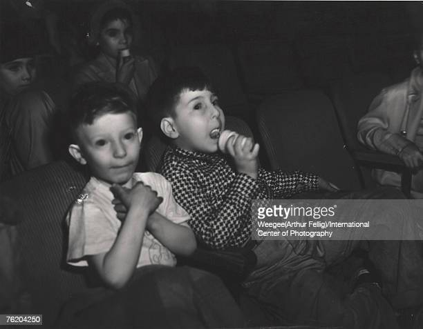 Infrared view of two young boys, one of whom licks and ice cream cone, as they watch a movie in a theatre, New York, New York, early 1940s.