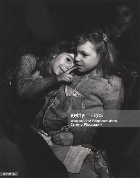 Infrared view of two young girls at a movie theatre one leans on the other's shoulder and holds a finger to the other's lips New York New York early...