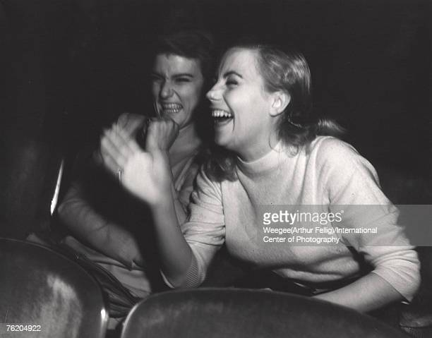 Infrared view of two young women who laugh while they watch a movie in a theatre New York New York early 1940s Photo by Weegee/International Center...
