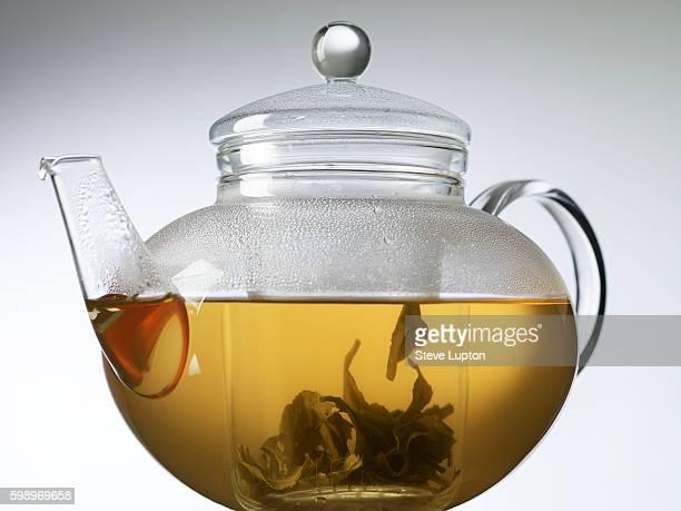 infusing gunpowder tea in a glass teapot - ティーポット ストックフォトと画像