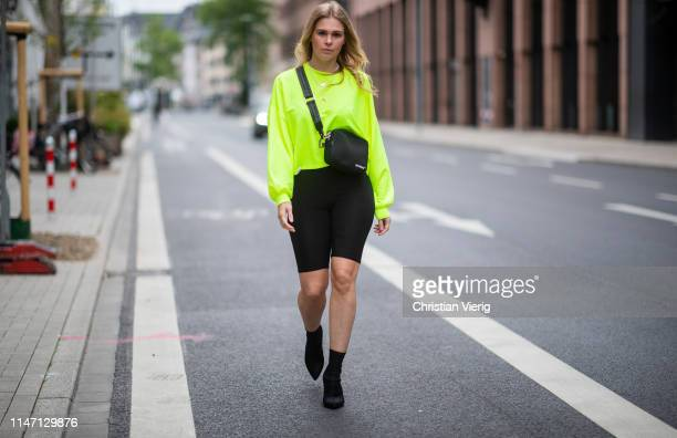 Inga Brauer is seen wearing black cycle pants Stradivarius neon sweater Bershka x Pantone Off White bag other stories sock boots on May 04 2019 in...