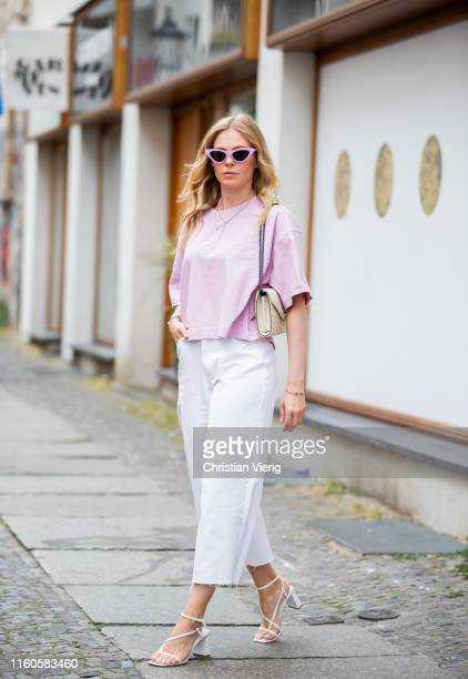 Inga Brauer is seen wearing white culotte Missguides, pink Acne Studios tshirt, white sandals Topshop, YSL bag on July 06, 2019 in Berlin, Germany.