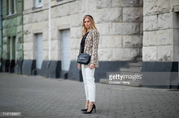 Inga Brauer is seen wearing white pants black ripped off top and blazer with snake print Zara Balenciaga bag Bershka pumps on May 04 2019 in...