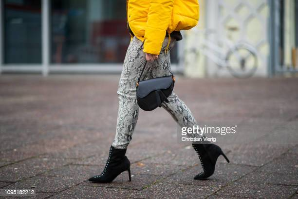 Inga is seen wearing yellow hooded down feather jacket Dior saddle bag pants with snake print black ankle boots during the Berlin Fashion Week...