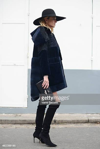 Inga Kozel poses wearing a Dior coat Chanel hat Manolo Blahnik shoes and Hermes bag during day two of Paris Haute Couture Spring Summer 2015 on...