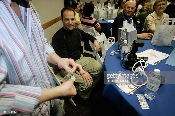 A magician teaches a magic trick to an attendee of entertainer David Copperfield's event of magicians physical therapists and patients at the...