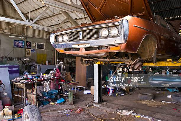 An old car rests on a hoist for repairs in a messy country workshop.