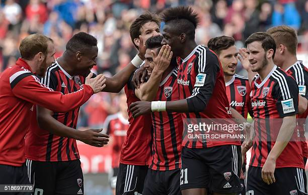 Ingolstadt's Paraguayan forward Dario Lezcano is congratulated by teammates after scoring his team's third goal during the German first division...