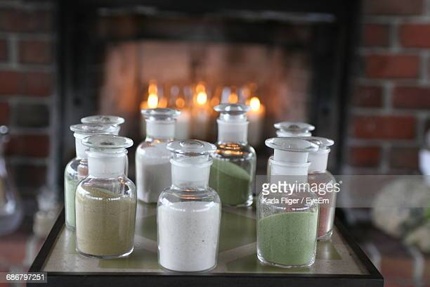 Ingredient In Jars On Table Against Illuminated Candles