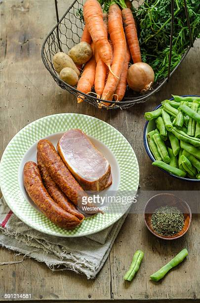 ingredients for bean stew, minced pork sausage and smoked pork chop on plate, carrot, potato, onion and herbs in basket - bush bean stock photos and pictures