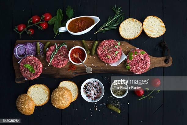 Ingredients for cooking burgers. Raw ground beef meat cutlets on wooden chopping board, red onion, cherry tomatoes, greens, pickles, tomato sauce, cheese, herbs and spices over black background, top view.