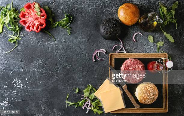 Ingredients for cooking hamburger Meat beef burger board cheese ketchup sauce tomato black and white buns arugula salad over dark texture background...