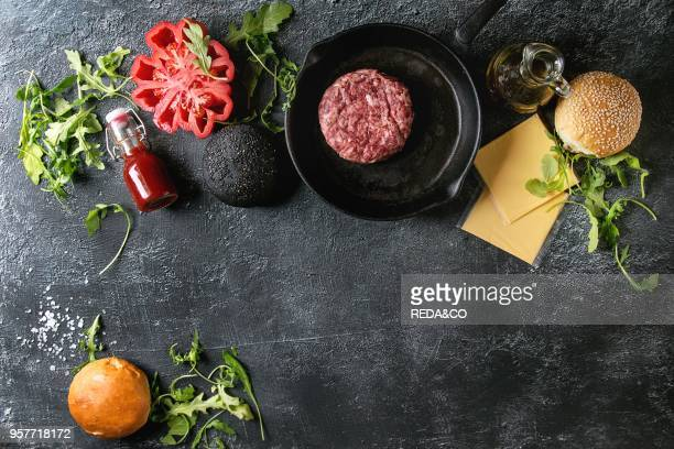 Ingredients for cooking hamburger Meat beef burger in pan cheese ketchup sauce tomato black and white buns arugula salad over dark texture background...
