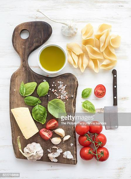 Ingredients for cooking pasta. Conchiglioni, basil leaves, cherry-tomatoes, Parmesan cheese, olive o