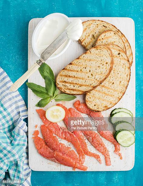 Ingredients for healthy sandwich. Grilled bread slices, smoked salmon, cottage cheese, cucumber and basil on turquoise wooden board