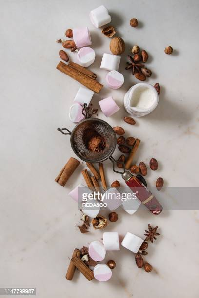 Ingredients for hot chocolate White pink big marshmallow cocoa beans cocoa powder cinnamon cream chopped chocolate nuts over white marble background...