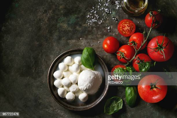 Ingredients for italian caprese salad Mozzarella balls buffalo in metal vintage plate tomatoes basil leaves olive oil with vinegar over dark...