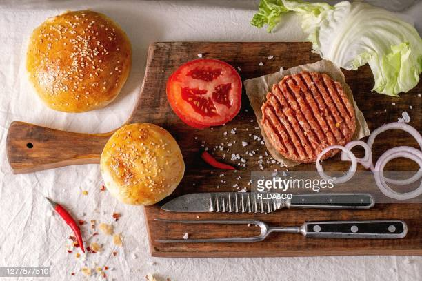 Ingredients for making homemade burger on wooden cutting board served with meat fork and knife over White tablecloth Dark rustic style Flat lay