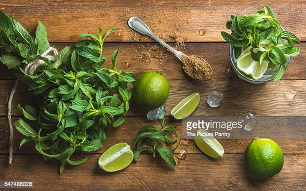 Ingredients for making mojito summer cocktail. Fresh mint bunch, limes, brown sugar and ice over rustic wooden background, top view